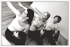 three women praticing yoga; stretching out their right arms